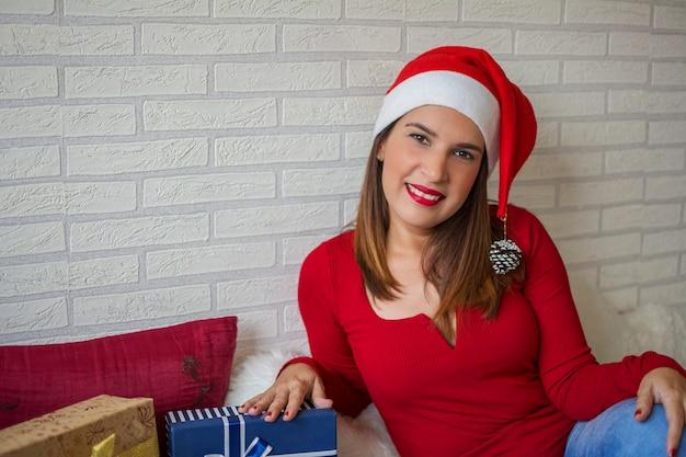 Mulher vestida de vermelho com chapéu de papai noel, sorrindo e feliz ao lado de seus presentes de natal. Foto Premium