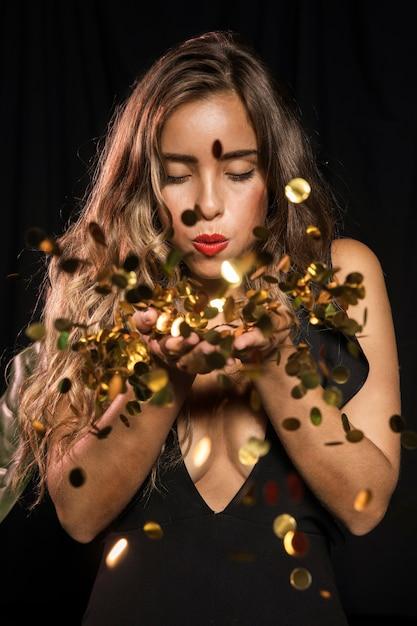 Mulher vestida para festa soprando em confete dourado Foto gratuita