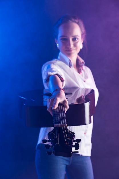 Mulher vestindo camisa de escritório, mostrando um violão Foto gratuita
