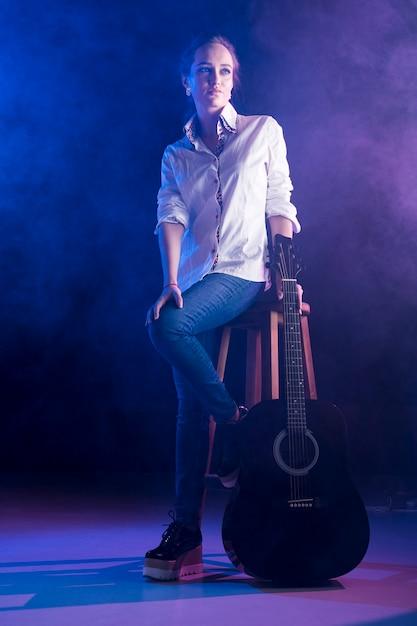 Mulher vestindo camisa de escritório segurando um violão Foto gratuita