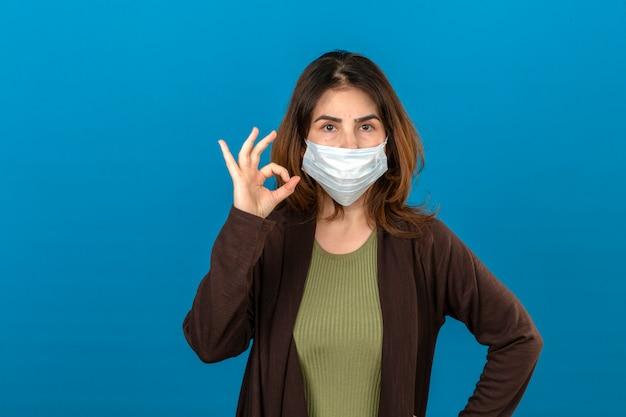 Mulher vestindo casaco de lã marrom na máscara protetora médica, olhando confiante, fazendo sinal de ok em pé sobre parede azul isolada Foto gratuita