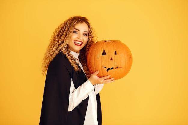 Mulher vestindo fantasia preta. senhora com maquiagem de halloween. garota de pé sobre um fundo amarelo. Foto gratuita