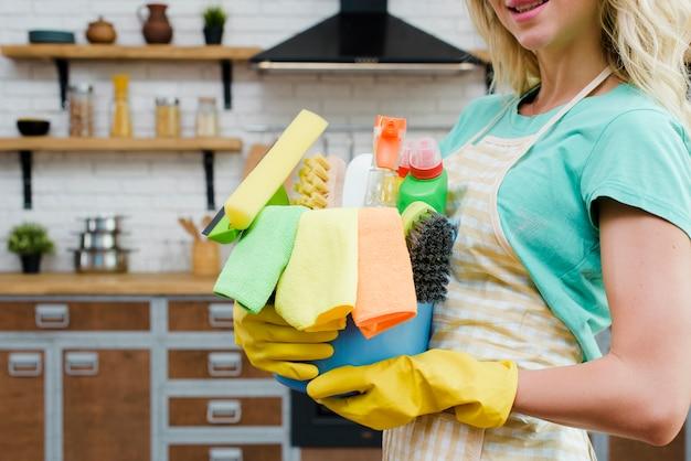 Mulher vestindo luvas de borracha amarela segurando produtos de limpeza em casa Foto Premium