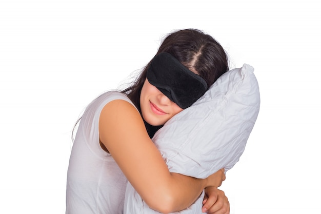 Mulher vestindo máscara de dormir e segurando um travesseiro. Foto gratuita