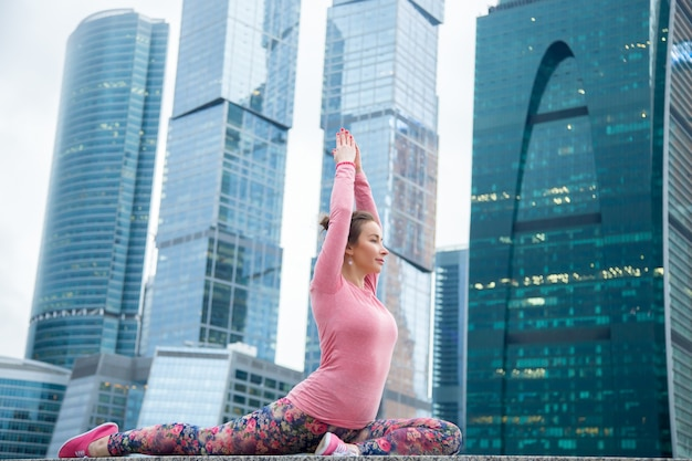 Mulher vestindo roupas esportivas rosa em pose de pombo-rei com uma perna Foto gratuita