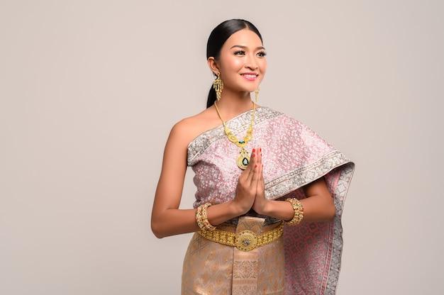 Mulher vestindo roupas tailandesas que pagam respeito Foto gratuita