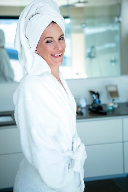 Mulher vestindo um roupão e uma toalha na cabeça está sorrindo Foto Premium