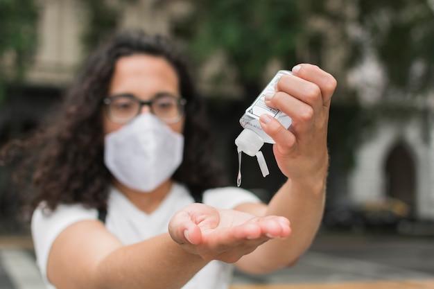 Mulher vestindo uma máscara médica usando desinfetante para as mãos Foto gratuita
