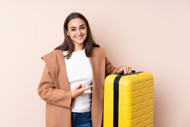 Mulher viajante com mala e apontando-o Foto Premium