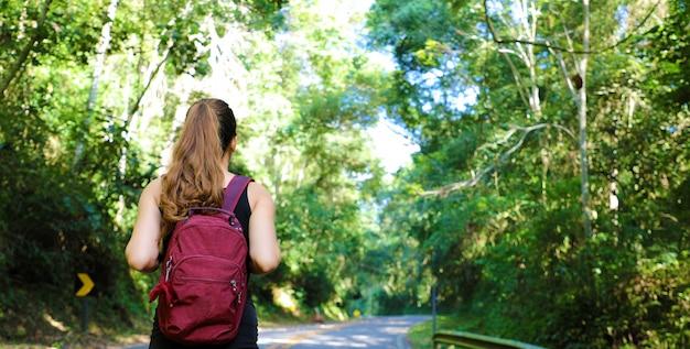 Mulher viajante com mochila caminhando em trilha de floresta tropical no brasil Foto Premium
