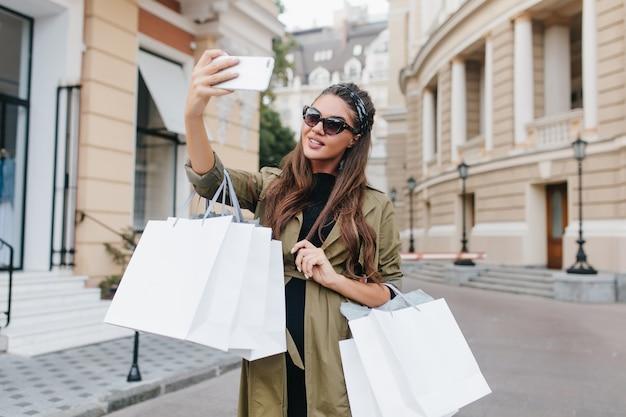 Mulher viciada em compras com pele bronzeada fazendo selfie no fim de semana Foto gratuita