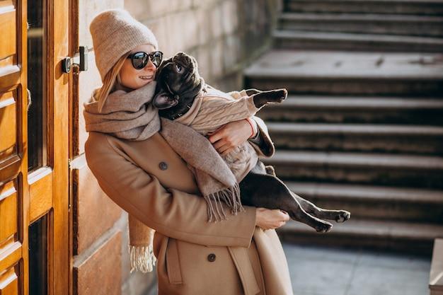 Mulher withg seu buldogue francês de estimação saindo Foto gratuita