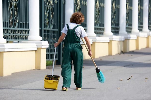 Mulher zeladora limpa a calçada da cidade de folhas caídas Foto Premium