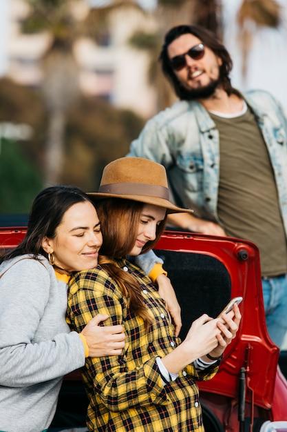 Mulheres alegres abraçando senhora com smartphone perto de mala de carro e o homem inclinando-se do automóvel Foto gratuita