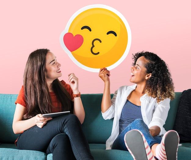 Mulheres alegres, segurando um ícone de emoticon beijando Foto gratuita