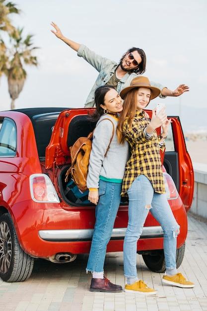 Mulheres alegres, tendo selfie no smartphone perto de mala de carro e o homem inclinando-se de auto Foto gratuita