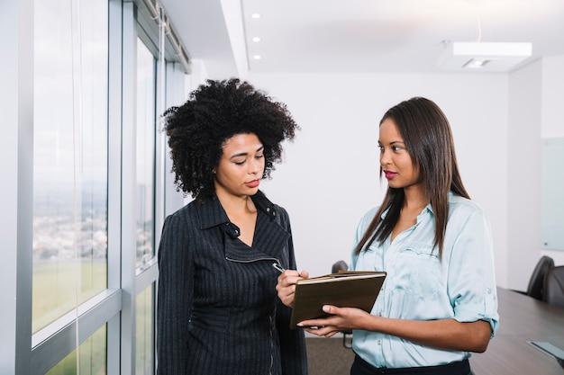 Mulheres americanas africanas, com, documentos, perto, janela, em, escritório Foto gratuita