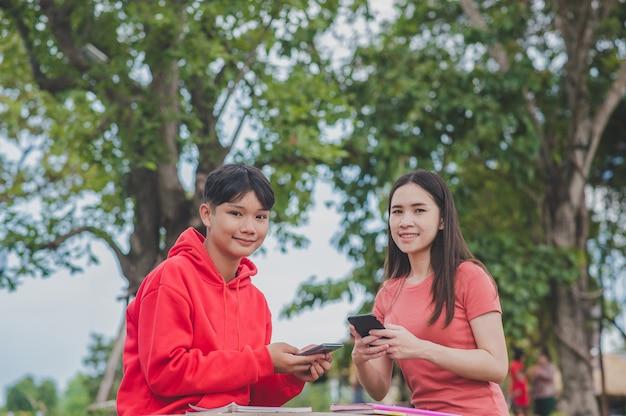 Mulheres asiáticas com lady boy lgbt estão usando a tecnologia on-line de pesquisa de aprendizagem de aulas de estudo para celular, conceito de educação de volta à escola Foto Premium