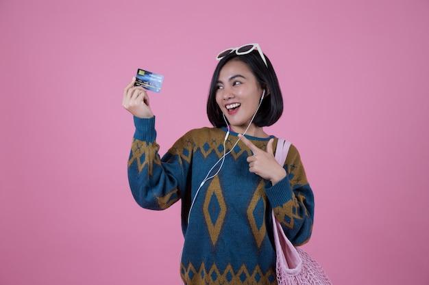 Mulheres asiáticas com óculos de sol, bolsa rosa e fone de ouvido mostrando cartões de crédito. Foto Premium