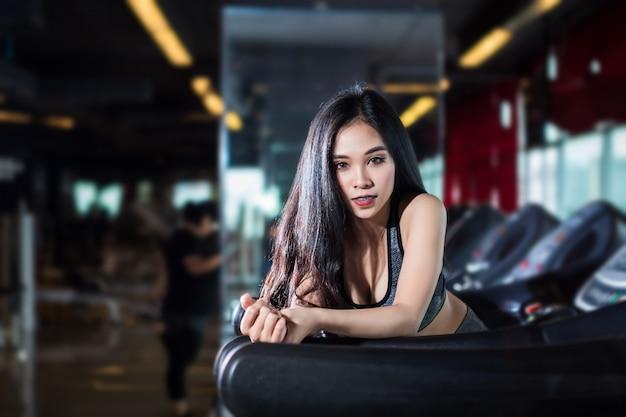 Mulheres asiáticas da aptidão que executam fazendo exercícios que treinam o funcionamento na escada rolante Foto Premium