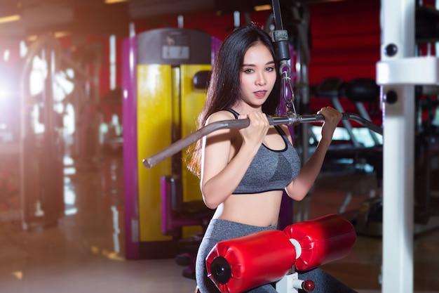 Mulheres asiáticas da aptidão que executam fazendo exercícios que treinam os músculos do ombro e da caixa no interior e no health club do gym do esporte Foto Premium