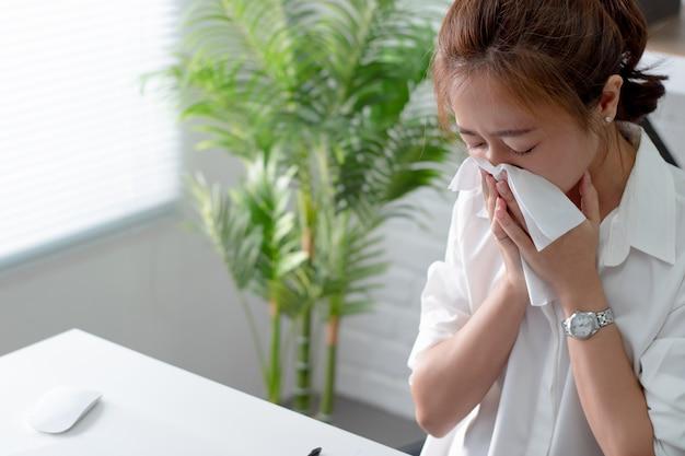 Mulheres asiáticas espirrando e com frio. ela está no escritório. Foto Premium