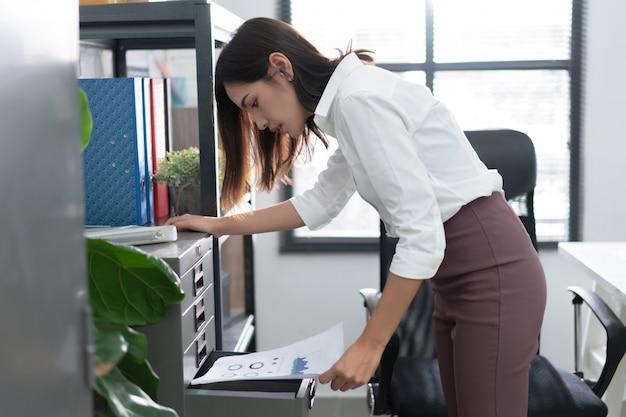 Mulheres asiáticas exibindo documentos no escritório Foto Premium