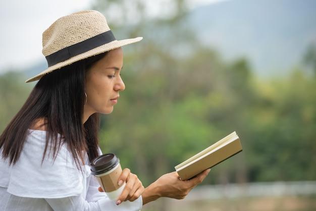 Mulheres asiáticas ler livros e beber café no parque. Foto gratuita
