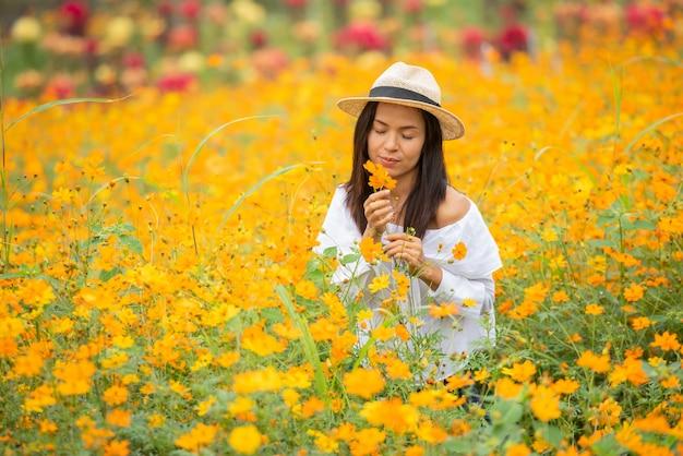 Mulheres asiáticas na fazenda de flores amarelas Foto gratuita