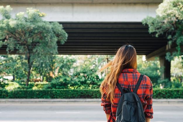 Mulheres asiáticas novas que estão ao longo da rua que aprecia seu estilo de vida da cidade em uma manhã Foto gratuita