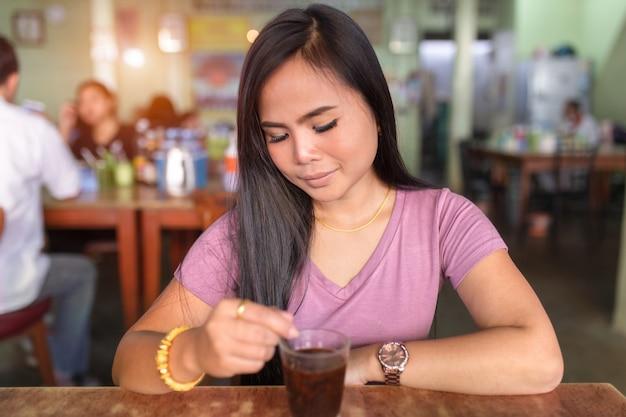 Mulheres asiáticas que bebem o vidro do café que senta-se na cafetaria. Foto Premium
