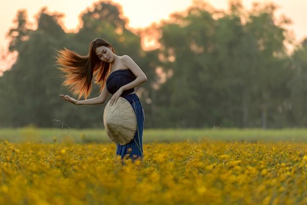 Mulheres asiáticas que estão em um campo de flor amarelo bonito. Foto Premium