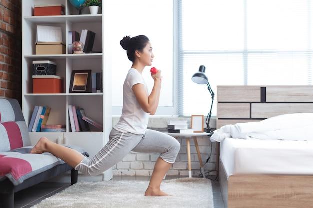 Mulheres asiáticas que exercitam na cama na manhã, ela sente refrescada. atua como o agachamento. Foto Premium