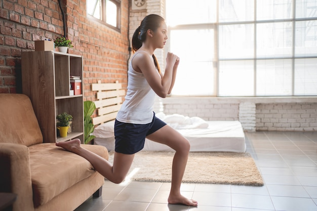 Mulheres asiáticas se exercitando no quarto pela manhã, ela se sente revigorada. Foto gratuita