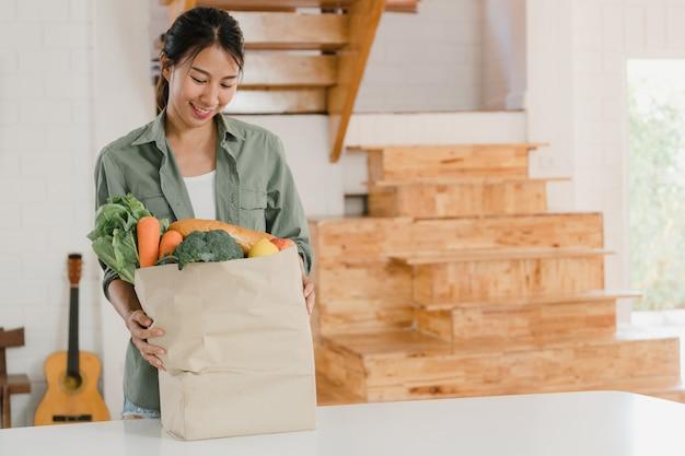 Mulheres asiáticas segurando sacolas de papel de compras na mercearia em hom Foto gratuita