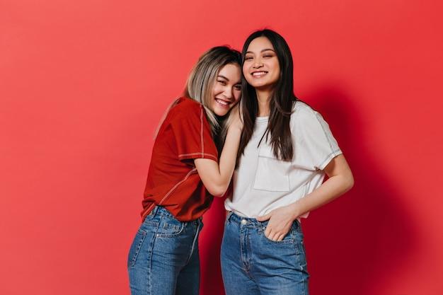 Mulheres asiáticas sorridentes posam na parede vermelha Foto gratuita