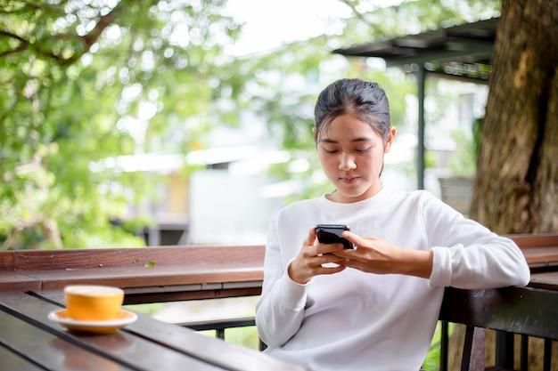 Mulheres asiáticas, usando mensagens de escrita em um telefone celular na loja de café Foto Premium