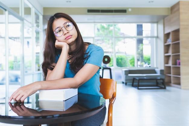 Mulheres asiáticas usando óculos estão entediados depois de ler livros na biblioteca Foto Premium