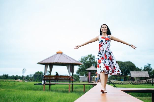 Mulheres bonitas andam alegremente na ponte de madeira Foto gratuita