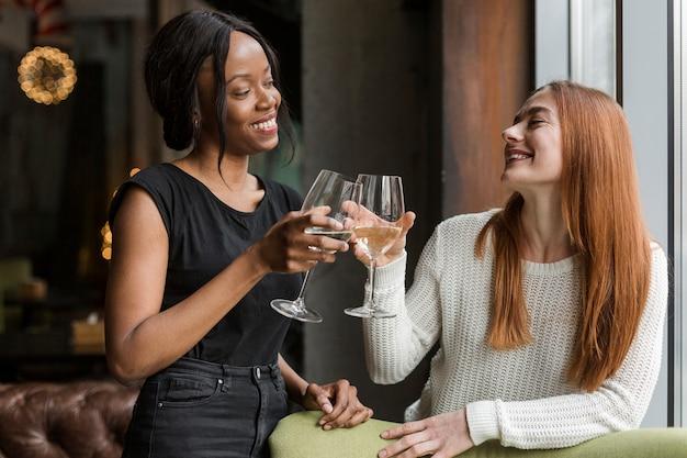 Mulheres bonitas brindando com taças de vinho Foto gratuita