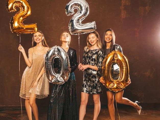 Mulheres bonitas comemorando o ano novo. meninas lindas felizes em elegantes vestidos de festa sexy segurando balões de ouro e prata 2020, se divertindo na festa de véspera de ano novo. celebração do feriado. Foto gratuita