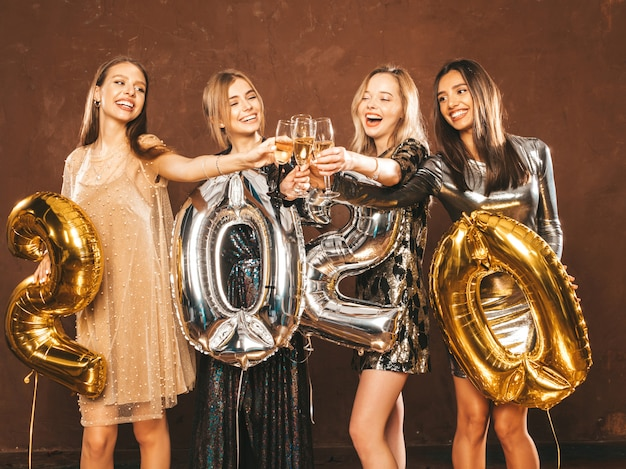 Mulheres bonitas, comemorando o ano novo. meninas lindas felizes em elegantes vestidos de festa sexy Foto gratuita