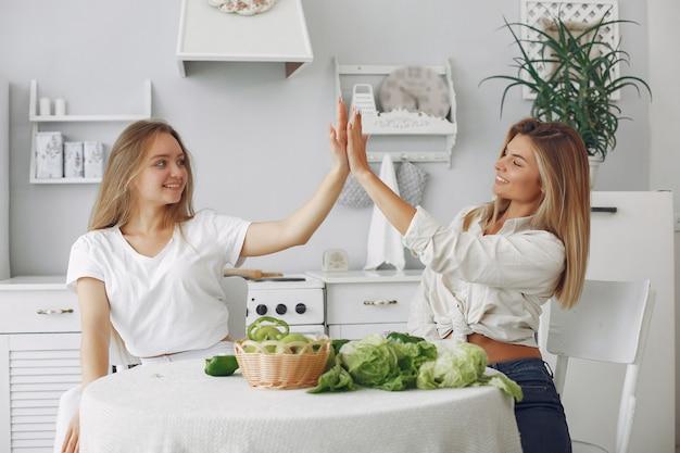 Mulheres bonitas e desportivas em uma cozinha com legumes Foto gratuita