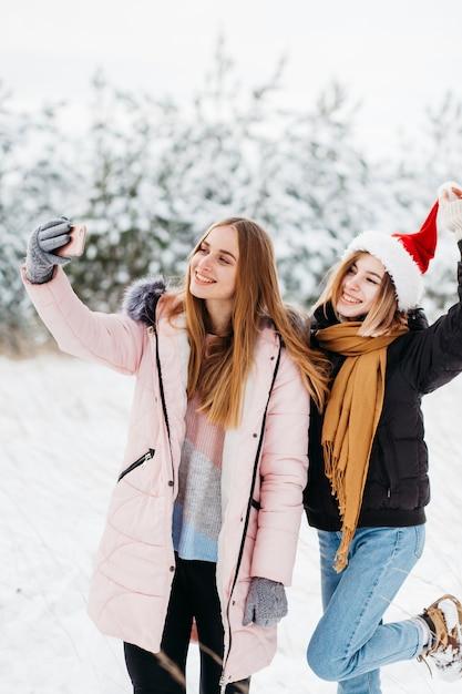 Mulheres bonitas no chapéu de papai noel tomando selfie na floresta de inverno Foto gratuita