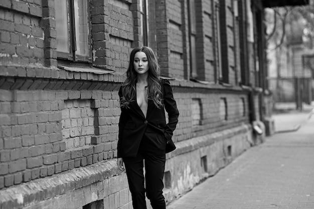 Mulheres bonitas sexy. garota fashion em um terno preto perto da parede de tijolo. streetwear das mulheres 2020. mulher de estilo de rua. como se vestir nesta primavera de 2020 Foto Premium