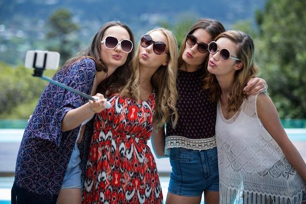 Mulheres bonitas tomando uma selfie perto da piscina Foto Premium