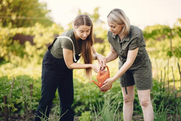 Mulheres bonitas trabalha em um jardim perto da casa Foto gratuita