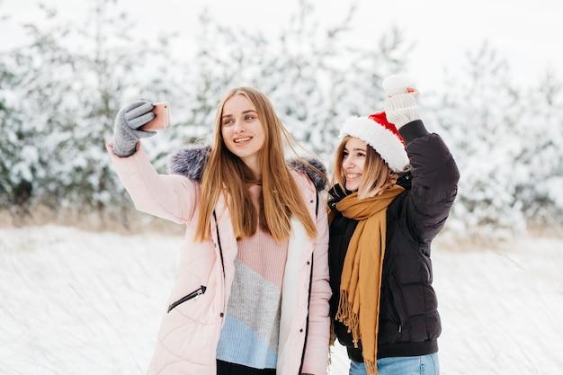 Mulheres bonitos no chapéu de papai noel tomando selfie na floresta de inverno Foto gratuita