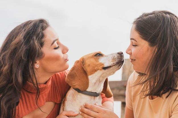 Mulheres brincando com cachorro Foto gratuita
