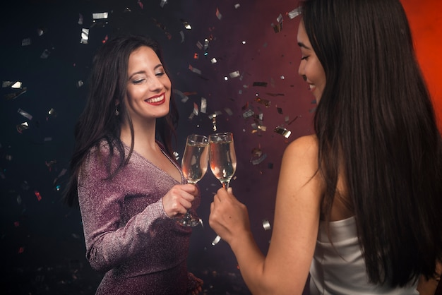 Mulheres brindando com champanhe na festa de ano novo Foto gratuita